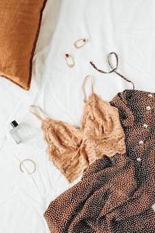 Modecollage mit trendiger damenunterwäsche und accessoires: bh, kleid, ohrringe, parfüm, armband und kissen auf weißem leinen
