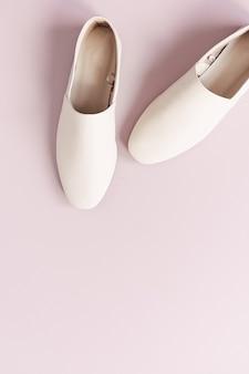 Modecollage mit weißen lederpantoffeln der frauen auf rosa. flache lage, draufsicht