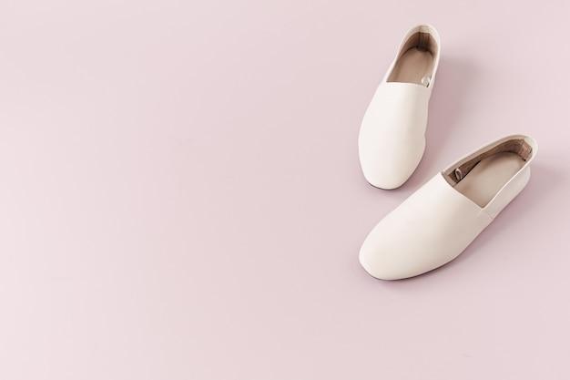 Modecollage mit weißen lederpantoffeln der frauen auf rosa