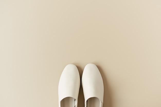Modecollage mit weißen lederpantoffeln für damen auf neutralem beige