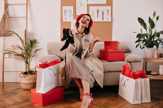 Modedame in der roten baskenmütze und im beigen mantel lacht und hält schwarze sandalen. freudiges junges mädchen mit dunklem haar genießt das einkaufen.