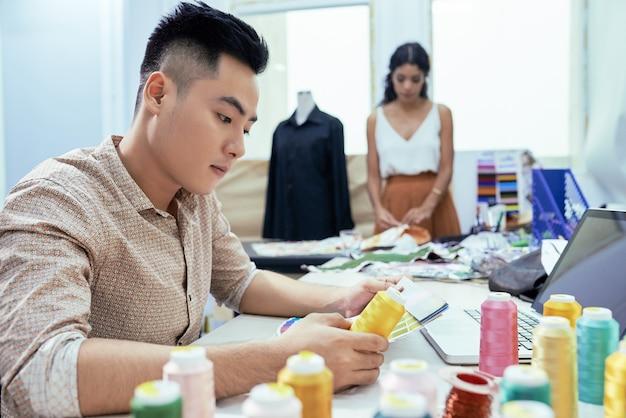 Modedesigner, der den perfekten farbton von gelben fäden wählt, wenn sein kollege im hintergrund ein kleid näht