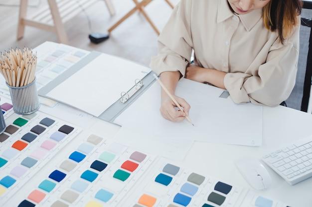 Modedesigner, der ein neues kleidungsmodell auf das papier zeichnet.