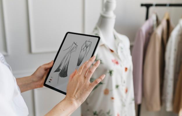 Modedesigner, der ein tablet mit einer designzeichnung hält