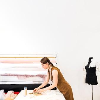 Modedesigner, der gewinde über werktisch wählt