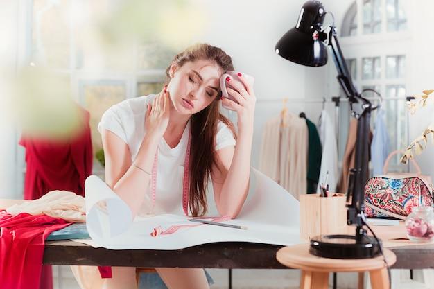 Modedesigner, der im studio arbeitet, das auf dem schreibtisch sitzt