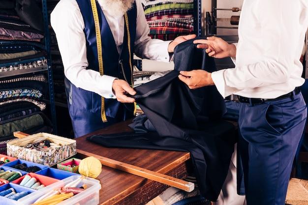 Modedesigner, der seinem kunden gewebe im shop zeigt