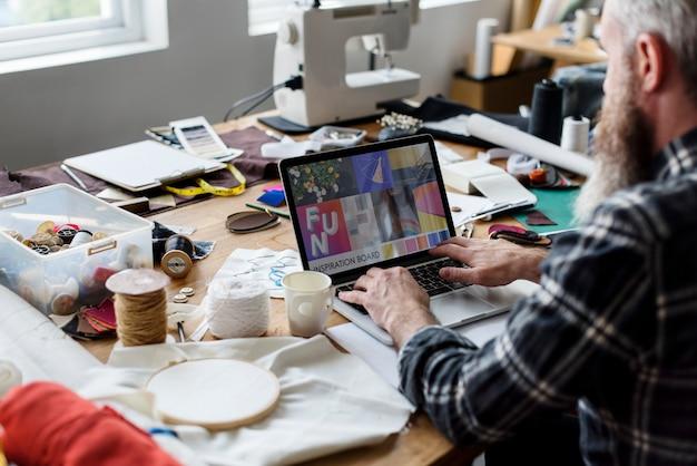 Modedesigner, der unter verwendung seines laptops arbeitet