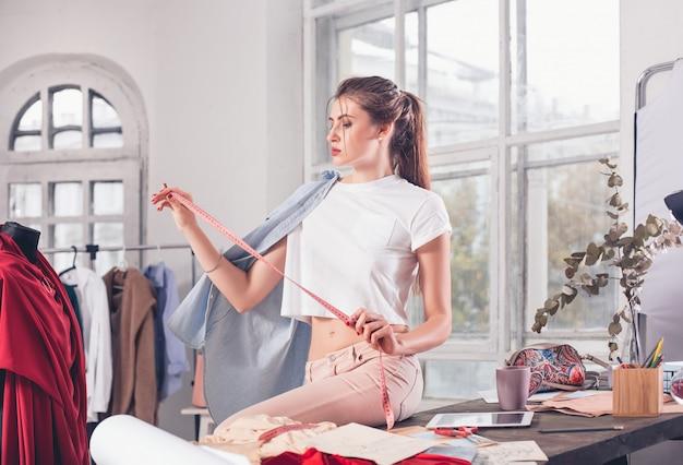 Modedesigner, die im studio arbeiten, das auf dem schreibtisch sitzt