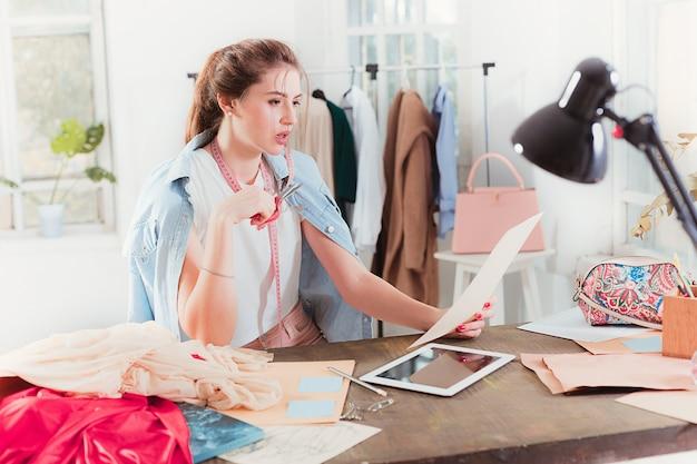 Modedesigner, die im studio arbeiten, sitzen auf dem schreibtisch