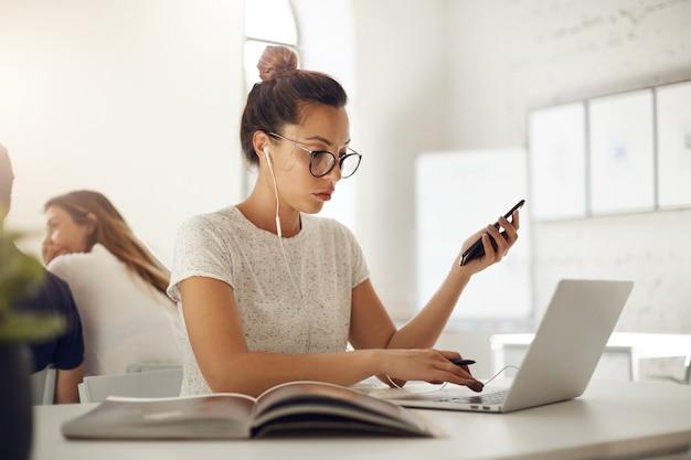 Modedesigner-geschäftsfrau, die an laptop-surfen für inspiration in einem hellen coworking-raum arbeitet, der online-musik unter verwendung des smartphones hört.