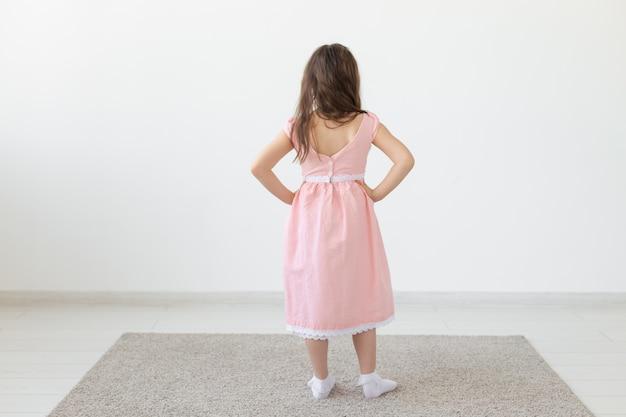 Modedesigner-, kinder- und kinderkonzept - rückansicht des kleinen mädchens, das in kleidern am studio aufwirft