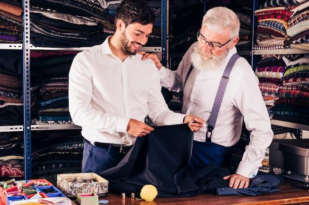Modedesigner und kunde, die gewebe in seinem shop betrachten