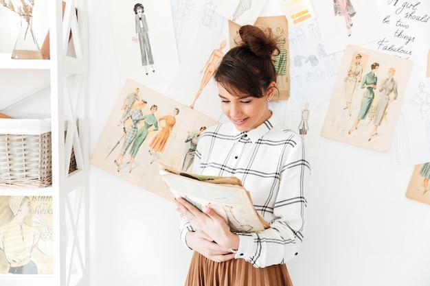 Modedesignerin der frau, die skizzenbuch hält, während an ihrem studio steht
