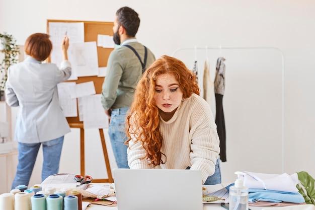 Modedesignerin, die im atelier mit kollegen und laptop arbeitet