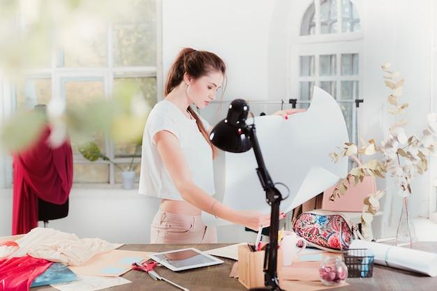 Modedesignerin, die im studio arbeitet, sitzt auf dem schreibtisch