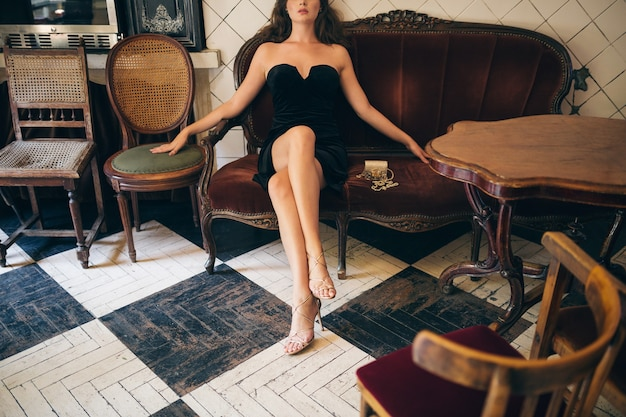 Modedetails der eleganten schönen frau, die im weinlesecafé im schwarzen samtkleid sitzt, reiche stilvolle dame, eleganter trend, lange dünne beine, hochhackige sandalenschuhe, schuhe tragen