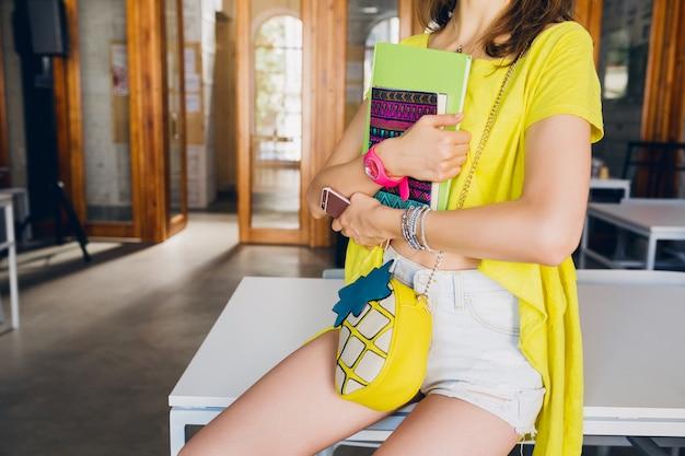 Modedetails der jungen hübschen frau, die am tisch im arbeitszimmer sitzt und notizbücher in händen hält, studentenlernen, bildung, bunter sommerhippestil, geldbörse