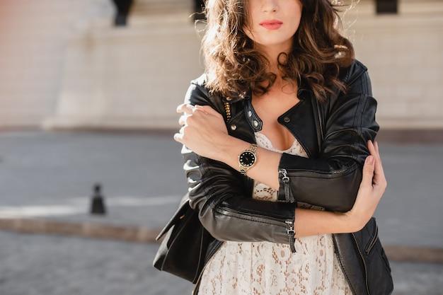Modedetails schließen oben von der attraktiven frau, die in der straße im modischen outfit trägt, das schwarze lederjacke und weißes spitzenkleid im frühlingsherbststil trägt, stilvolle uhr zur hand