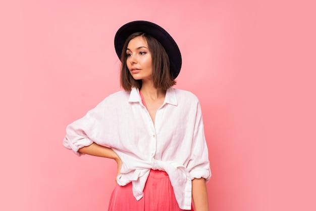 Modefoto der anmutigen brünetten frau im frühlingsoutfit, das weiße tasche hält.