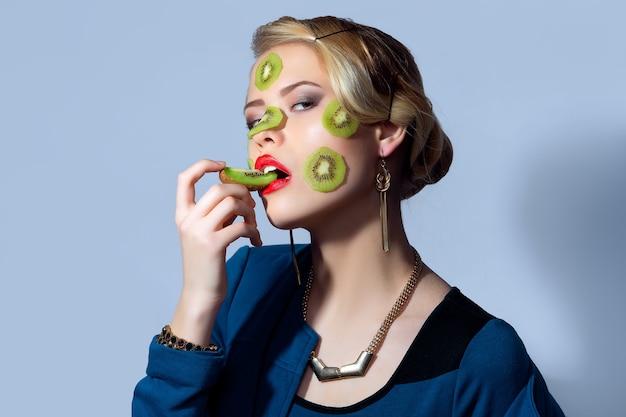 Modefoto der frau, die mit scheiben der kiwi auf ihrem gesicht aufwirft.