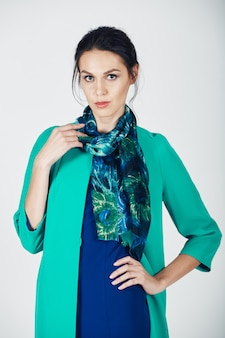 Modefoto der jungen ausgezeichneten frau in einem türkiskleid