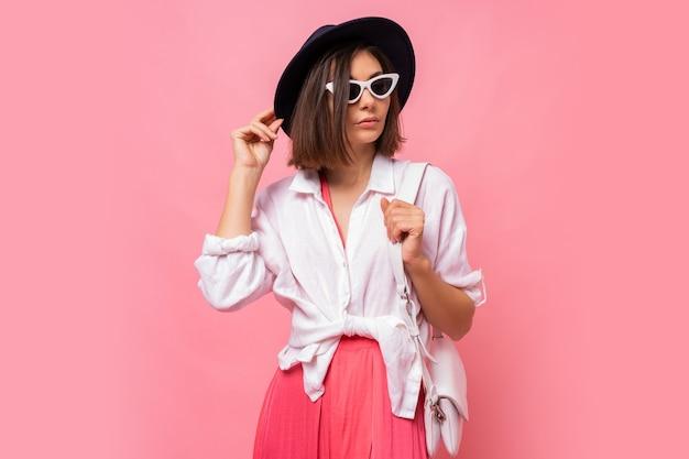 Modefoto der reizenden brünetten frau im frühlingsoutfit, das stilvolle sonnenbrillen aufwirft.