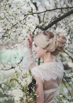 Modefoto der schönen blonden frau mit luxuriösem hochzeitskleid, das im blühenden frühlingsgarten aufwirft