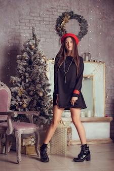 Modefoto der schönen frau mit dunklem haar im eleganten schwarzen kleid. weihnachtsbaum auf hintergrund