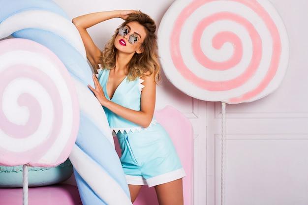 Modefoto der sexy schönen frau mit der blonden frisur, die trendiges blaues ledertop und shorts trägt, die nahe großen bunten requisitenbonbons sitzen. moderne junge modische dame in pastellfarben.