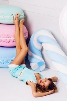 Modefoto der sexy schönen frau mit der blonden lockigen frisur, die trendiges blaues ledertop und shorts nahe großen bunten requisitenbonbons trägt. moderne junge modische dame in pastellfarben.