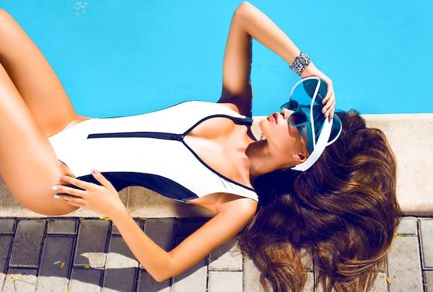 Modefoto des sexy schönen mädchens im schwarzen bikini, der neben einem schwimmbad entspannt, junge hübsche frau mit perfekt gegerbtem körper, der auf gelber luftmatratze im pool liegt und spaß hat