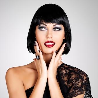 Modefoto einer schönen brünetten frau mit schussfrisur. nahaufnahme mädchengesicht mit roten lippen und nägeln