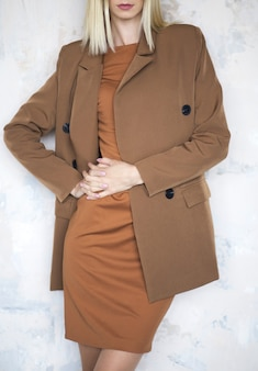 Modefoto einer schönen eleganten jungen frau in einem hübschen übergroßen braunen und beige anzug, der über weißem hintergrund aufwirft. studioaufnahme. vertikales foto