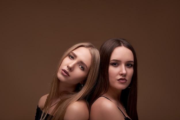 Modefoto von zwei schönen mädchen mit blonden haaren und nacktem make-up,