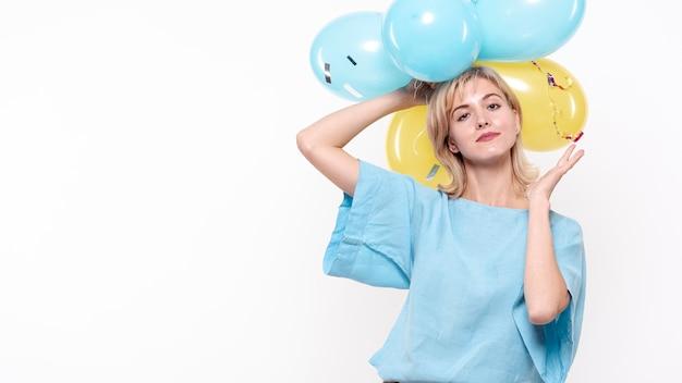 Modefotofrau, die ballone über kopf hält