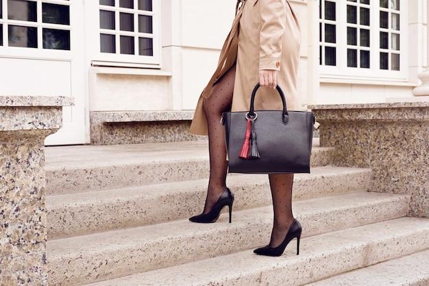 Modefrau auf treppen in schuhen mit hohen absätzen mit schwarzer handtasche. herbst im freien