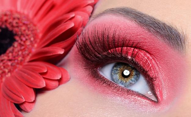 Modefrau auge mit rotem make-up und langen falschen wimpern - blume am hintergrund
