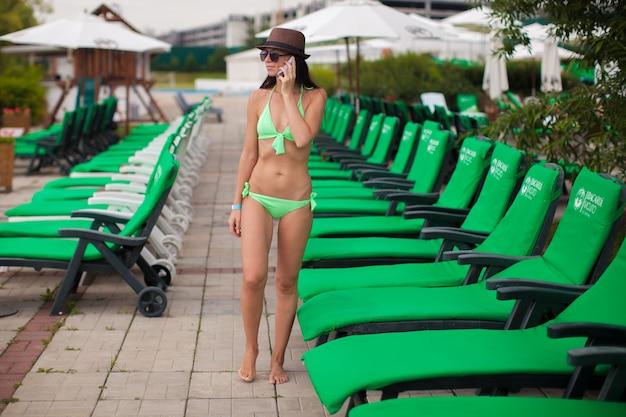 Modefrau, die am telefon beim gehen nahe swimmingpoolruhesessel spricht