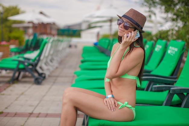 Modefrau, die am telefon beim sitzen am swimmingpoolruhesessel spricht