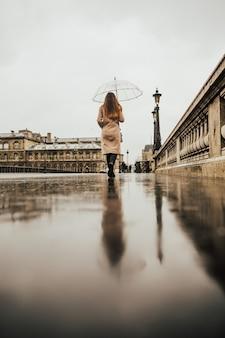 Modefrau, die eine brücke an einem regnerischen tag in paris überquert und einen transparenten regenschirm trägt.