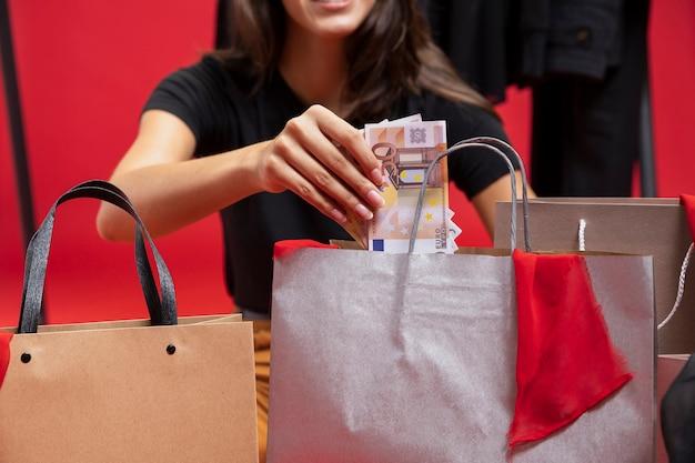 Modefrau, die geld in einkaufstaschen einsetzt