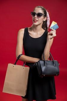 Modefrau, die ihre kreditkarten hält