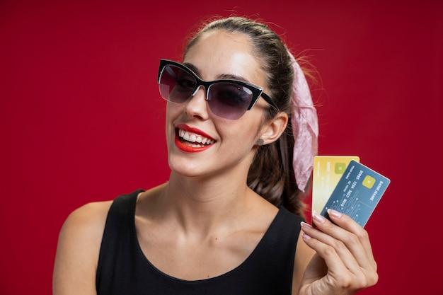 Modefrau, die ihre kreditkarten zeigt