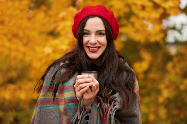 Modefrau, die im herbstpark geht, eingewickelt in karierte warme decke und rote baskenmütze, die thermoskanne tasse in den händen hält