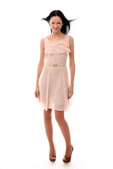Modefrau, die mit elegantem rosa kleid aufwirft