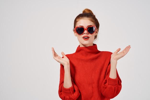 Modefrau im roten pullover gestikuliert mit ihren händen daumenmodell