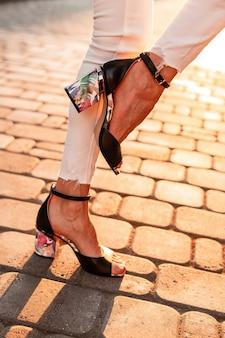 Modefrau in stilvollen schwarzen ledersandalen in jeans steht auf einem bein auf einer steinstraße auf der straße bei sonnenuntergang. nahaufnahme.