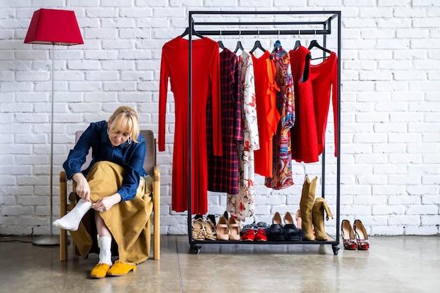Modefrau posiert mit kleiderständer voller trendiger kleidungsschuhe und accessoires im loft-studio
