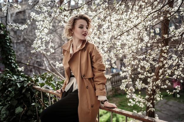Modefrauenporträt des jungen hübschen trendigen mädchens, das an der stadt in europa, frühlingsstraßenmode aufwirft. lachendes und lächelndes porträt. retro-stil, regenmantel und rote lippen
